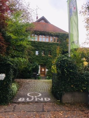 in einem verwunschenen Garten das BUND Haus mit goldenem Herbstlaub